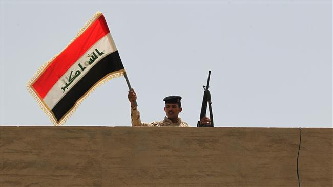 An Iraqi soldier waves the Iraqi national flag above a building in Saqlawiyah, northwest of Fallujah, June 8, 2016. (Photo by AFP)