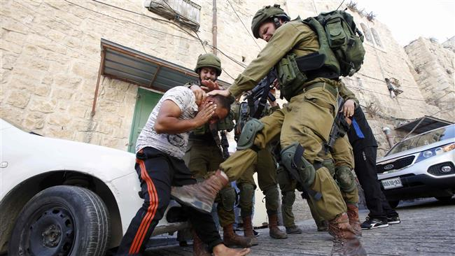 An Israeli soldier kicks a Palestinian man as troops try to arrest him in the southern West Bank city of al-Khalil (Hebron) on September 20, 2016. (Photo by AFP)