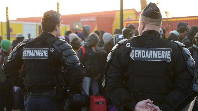 "Gendarms stand guard as asylum seekers queue during the full evacuation of the ""Jungle"" refugee camp in Calais, northern France, on October 25, 2016. (Photo by AFP)"