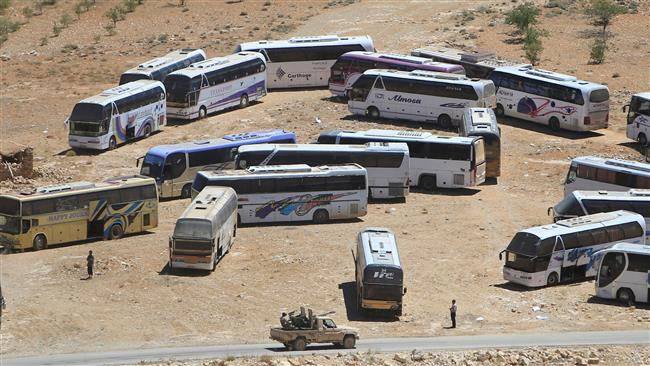 A military vehicle drives past parked buses that will transfer militants in the highlands of Arsal bordering with Syria on July 31, 2017. (Photo by Reuters)