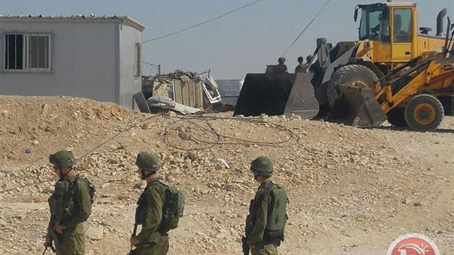 Israeli forces watch as Tel Aviv regime bulldozers demolish UN funded homes in a Bedouin village in the southern West Bank. (Photos by Ma'an)