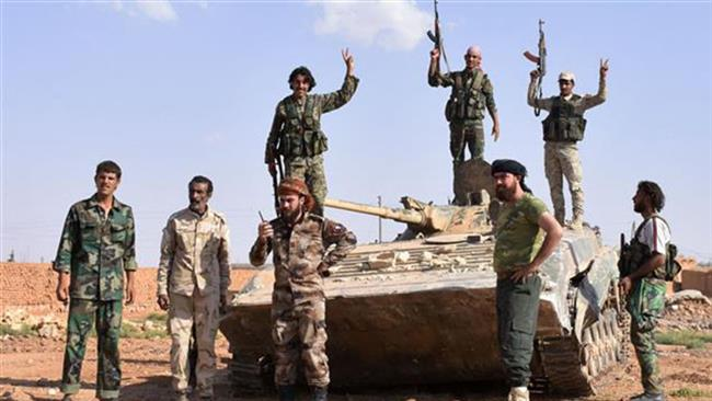 Syrian pro-government forces flash the victory sign on top of a tank after taking control of the northern Syrian town of Maskanah from Daesh terrorists on June 5, 2017. (Photo by AFP)