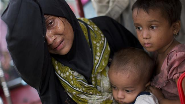 The photo shows an exhausted Rohingya woman arrives with her children at Kutupalong refugee camp after crossing from Myanmar to the Bangladesh side of the border, in Ukhia, on September 5, 2017. (Photo by AP)