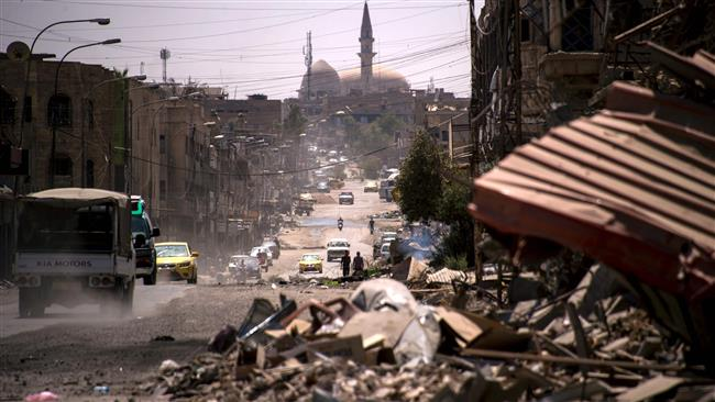 Cars drive along a damaged street in west Mosul on July 12, 2017, a few days after the government's announcement of the liberation of the embattled city from Daesh terrorists. (Photo by AFP)