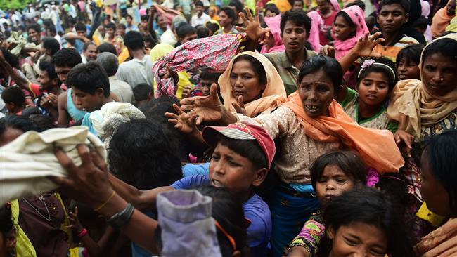 Newly arrived Rohingya refugees scuffle for relief supplies at Kutupalong camp in the Bangladeshi locality of Ukhia on September 9, 2017. (Photo by AFP)