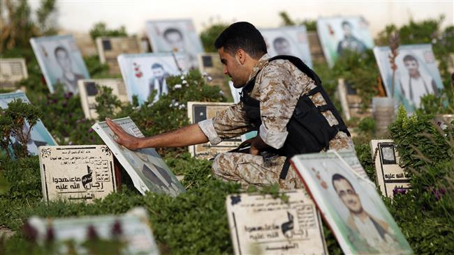 A Yemeni man touches the portrait of a loved one while squatting on top of his grave at a cemetery in the capital Sana'a on September 1, 2017. (Photo by AFP)