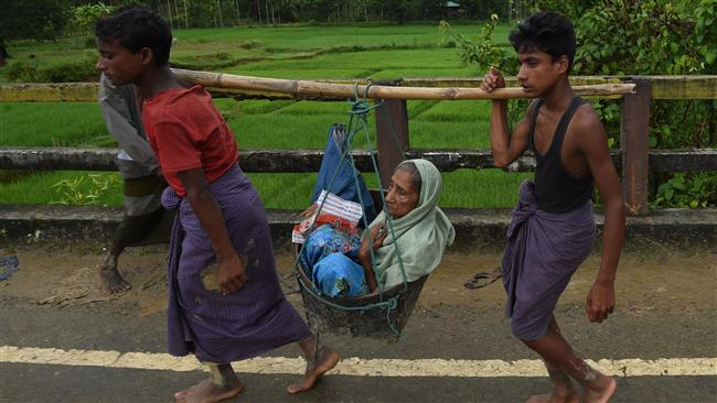 Rohingya Muslim refugees carry an elderly woman along a road near Balukhali refugee camp close to the Bangladeshi district of Ukhia on September 19, 2017. (Photo by AFP)