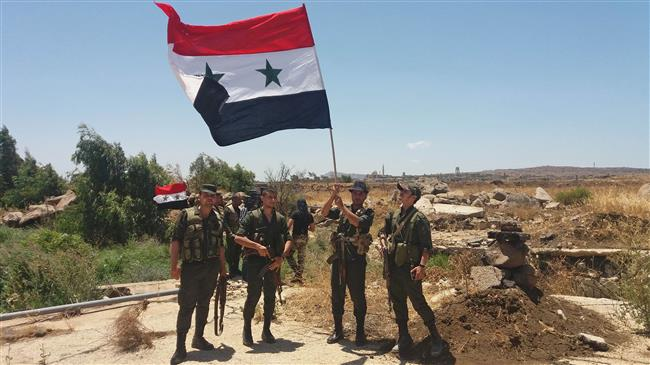 A handout picture released by the official Syrian Arab News Agency (SANA) on July 26, 2018 shows Syrian army soldiers carrying the national flag in the village of Hamidiya in the southern province of Quneitra.
