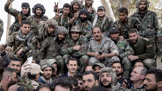 A file photo of Syrian President Bashar al-Assad (C) among a group of army soldiers