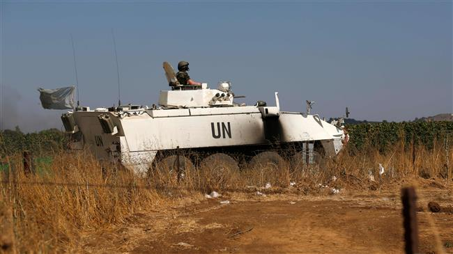 A peacekeeper from the UN Disengagement Observer Force (UNDOF) stationed in the Israeli-occupied Golan Heights sits in an infantry fighting vehicle while on patrol near the Quneitra crossing checkpoint on July 20, 2018. (Photo by AFP)