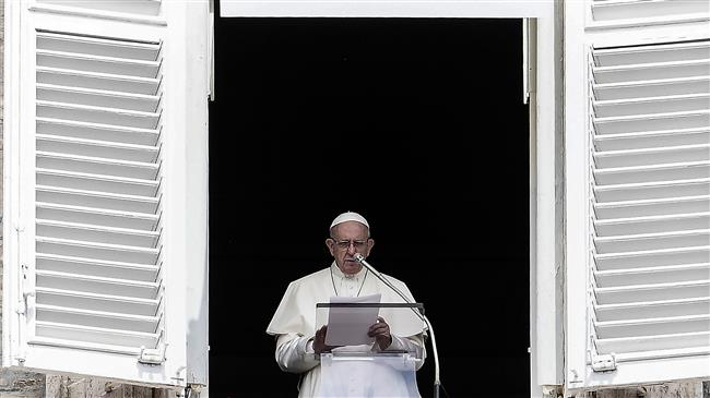 Pope Francis reads to pilgrims during The Angelus Prayer from the window of his studio overlooking St. Peter